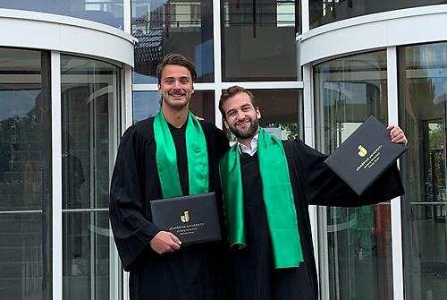 Niklas Koch and Sören Pongratz in their graduation gowns stand outside JIBS entrance. They have their arms around each other's shoulders and have their diplomas raised in the air. Both are smiling and looking out to the camera.